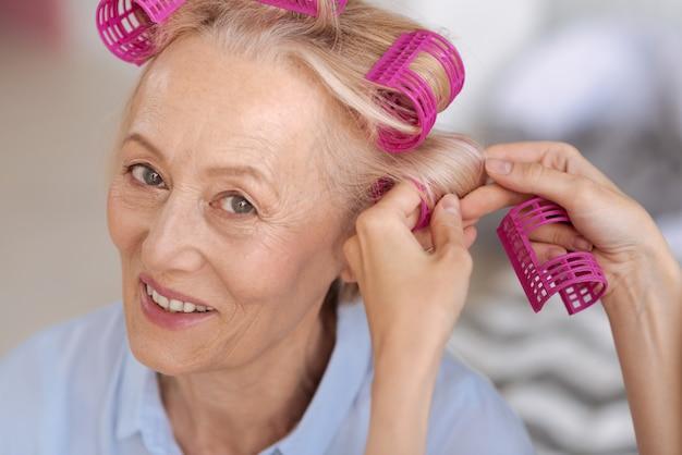 Aangename vrolijke oudere vrouw, met roze haarrollers, die wat hulp krijgt met een paar extra's terwijl ze naar voren kijkt en glimlacht