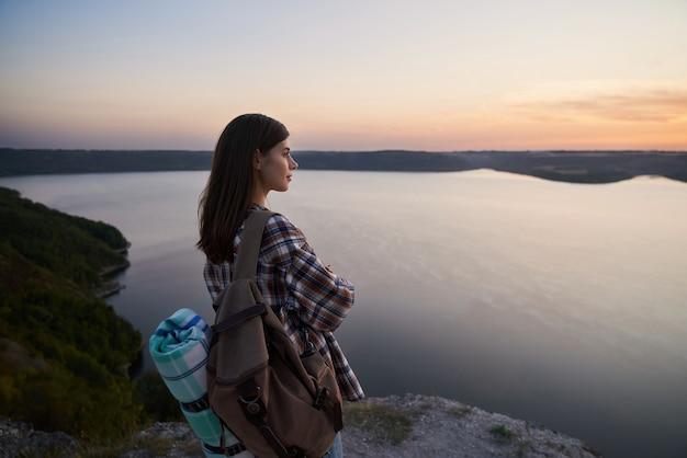Aangename vrouw die op een heuvel staat en naar de zonsondergang kijkt