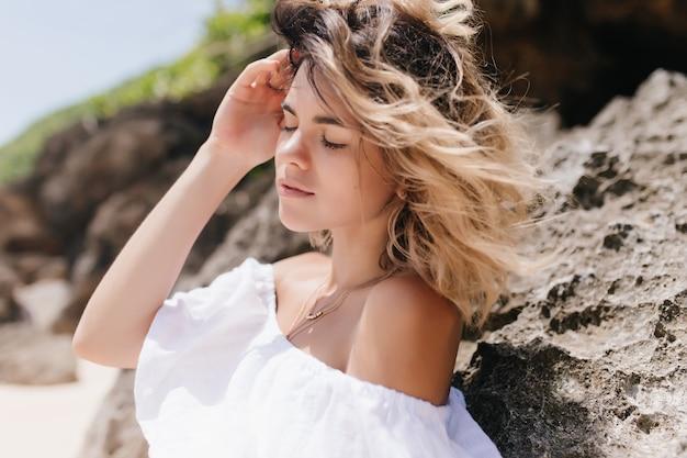 Aangename vrouw poseren in de buurt van rock met gesloten ogen. openluchtportret van gebruinde sensuele dame die zich op aard bevindt.