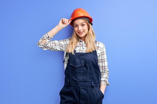 Aangename zelfverzekerde architectenvrouw in overall die over blauwe studiomuur wordt geïsoleerd