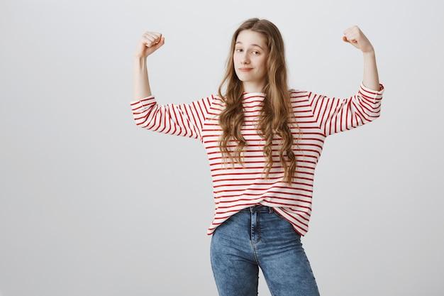 Aangename zelfvoldane meid buigt biceps, laat haar kracht zien