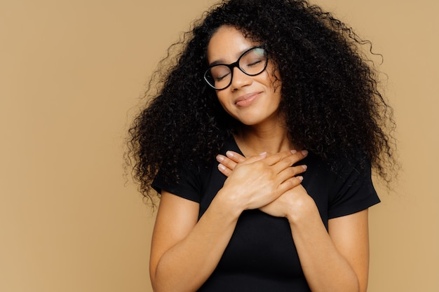 Aangeraakt mooie vrouw met afro-kapsel, houdt beide handpalmen op de borst, heeft ogen dicht voor plezier