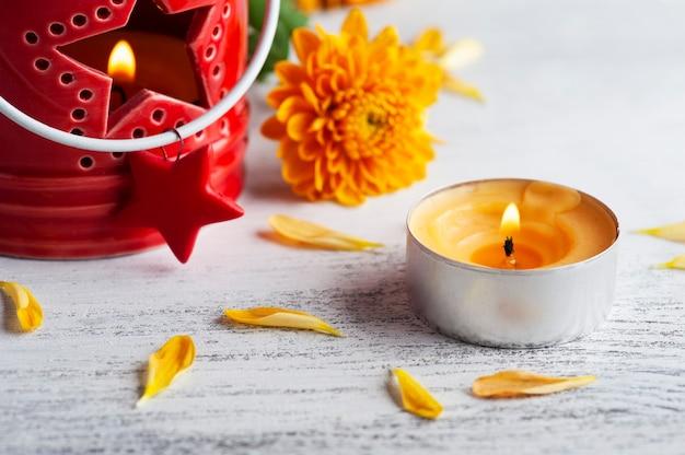 Aangestoken aroma rode kaars en oranje bloemen op rustieke achtergrond. wenskaart voor feest