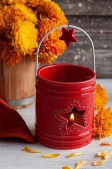 Aangestoken aroma rode kaars en oranje bloemen op rustieke tafel. wenskaart voor feest