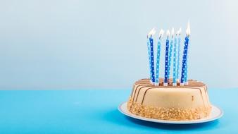 Aangestoken kaarsen over de heerlijke cake tegen blauwe achtergrond