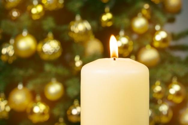Aangestoken kerstmiskaars tegen verfraaide boom