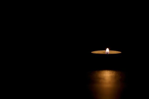 Aangestoken tinnen kaars in het donker die gedenkteken, dood, hoop of duisternis overbrengt