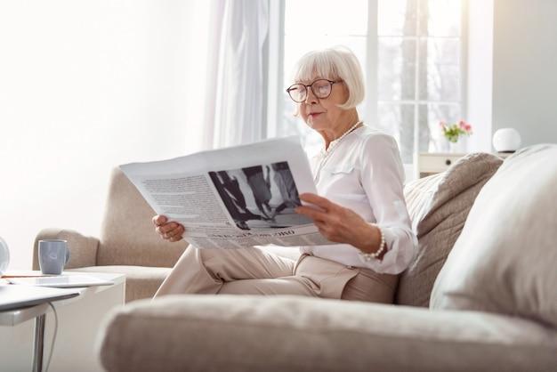 Aangrijpend artikel. kleine oudere vrouw die op de bank in de woonkamer zit en wordt ondergedompeld in het lezen van een interessant artikel