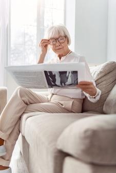 Aangrijpende inhoud. aangename oudere dame die op de bank zit en een interessante krant leest terwijl ze haar bril aanpast