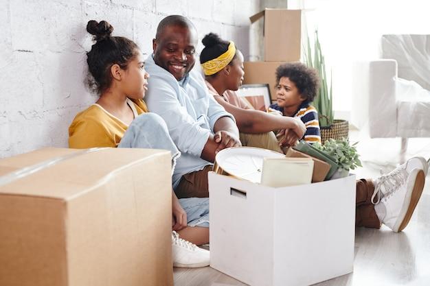 Aanhankelijk en gelukkig afrikaans gezin van vier in vrijetijdskleding zittend tegen een wit geschilderde muur op de vloer van de woonkamer en praten