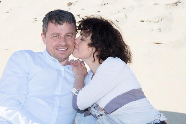 Aanhankelijk getrouwd stel van middelbare leeftijd ontspannen aan strand zee