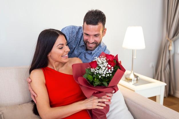 Aanhankelijk jonge man geeft zijn mooie jonge vrouw een boeket rode rozen op valentijnsdag