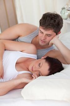 Aanhankelijk jonge man kijken naar zijn zwangere vrouw slapen beide liggend op het bed
