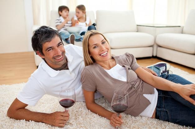 Aanhankelijk liefhebbers die wijn drinken die op de vloer ligt