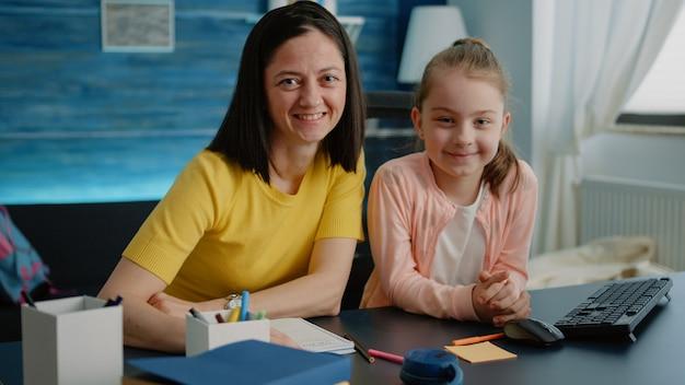 Aanhankelijk moeder zit aan bureau met dochter voor huiswerk