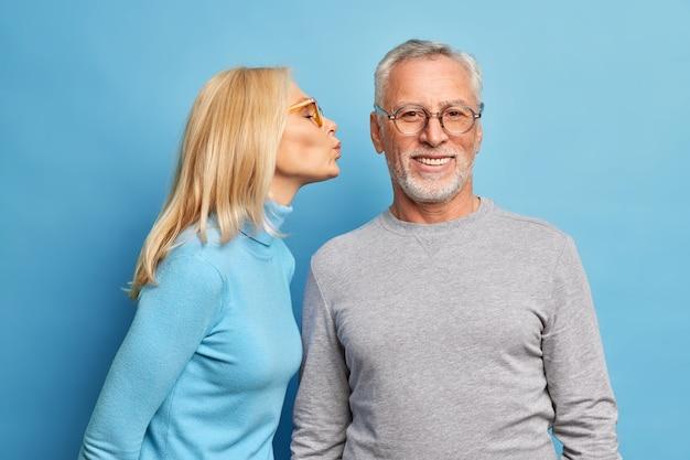 Aanhankelijk oudere blonde vrouw gaat bebaarde man in wang kussen spreekt liefde uit