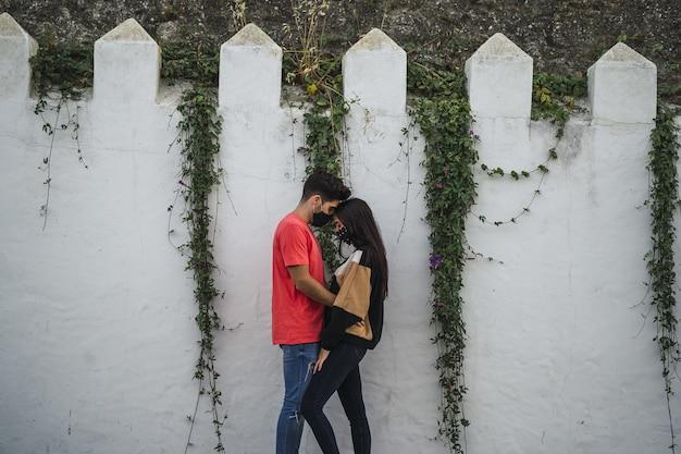 Aanhankelijk paar dat zich bij een versierde muur bevindt
