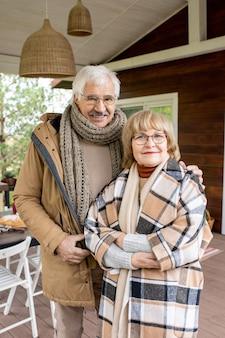 Aanhankelijk senior man en vrouw in warme vrijetijdskleding kijken je met een glimlach aan terwijl ze bij hun huis tegen de geserveerde tafel staan