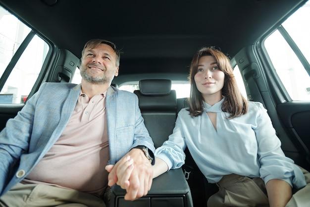 Aanhankelijke gelukkige man en vrouw van middelbare leeftijd die elkaar bij de hand houden terwijl ze op de achterbank van een nieuw automodel zitten tijdens een proefrit