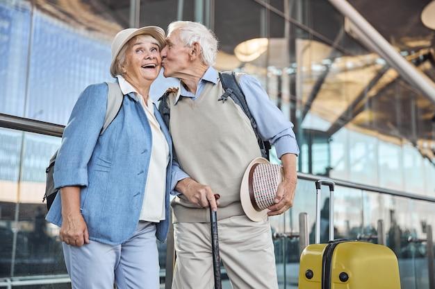 Aanhankelijke mannelijke echtgenoot met een wandelstok die zijn glimlachende tevreden aantrekkelijke vrouw teder op de wang kust