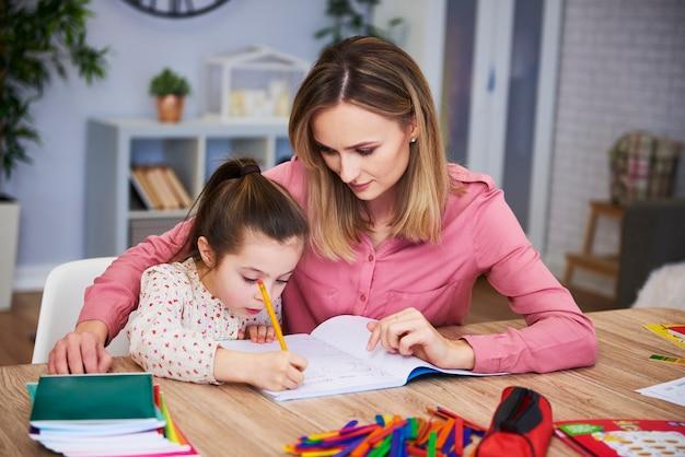 Aanhankelijke moeder helpt haar dochter met moeilijk huiswerk