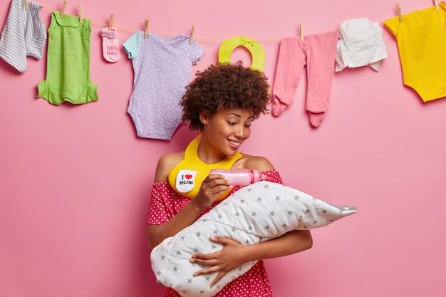 Aanhankelijke vrolijke moeder voedt pasgeboren baby uit de fles, heeft een blije uitdrukking, draagt een slabbetje in de nek, is een gelukkige moeder van een pas geboren kind, staat binnen