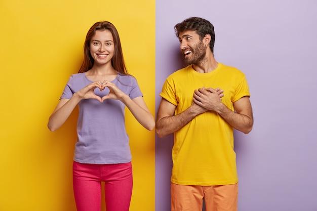 Aanhankelijke vrouw toont hartgebaar, zegt wees mijn valentijn tegen vriend, bekent verliefd