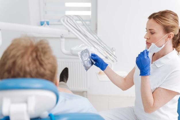 Aanhoudende, opmerkzame, nette arts die haar ervaring toepast tijdens het bestuderen van de kaakscan en het uitzoeken van de diagnose