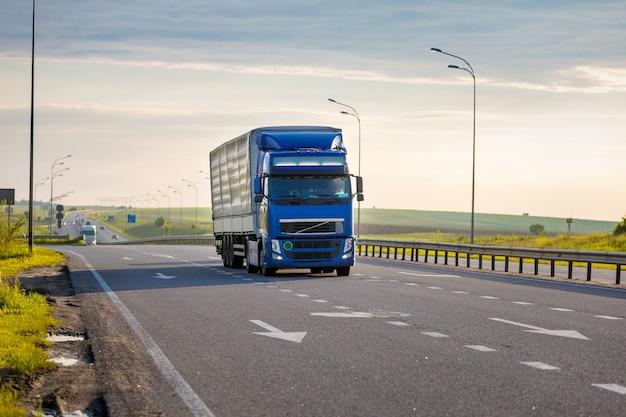 Aankomen blauwe vrachtwagen op weg in een landelijk landschap bij zonsondergang