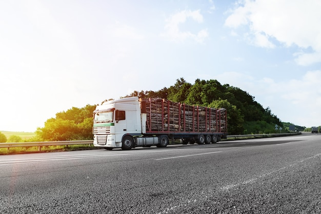 Aankomen witte vrachtwagen op de weg in een landelijk landschap bij zonsondergang