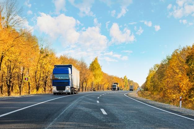 Aankomende blauwe vrachtwagen op de weg in een landelijk landschap bij zonsondergangherfst