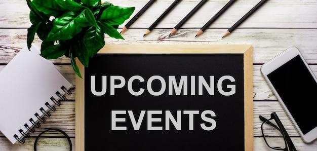 Aankomende evenementen is in het wit geschreven op een zwart bord naast een telefoon, notitieblok, bril, potloden en een groene plant