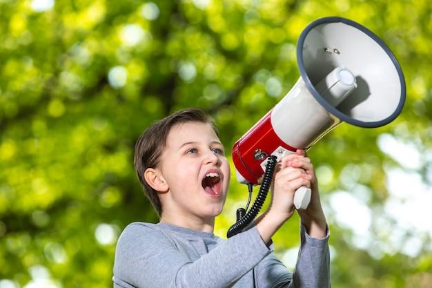 Aankondigend concept, jongen die door de megafoon over bos schreeuwt of schreeuwt