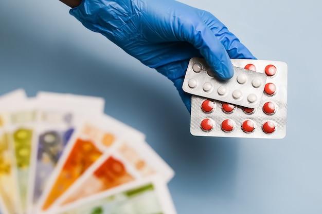 Aankoop van medicijnen, pillen voor euro's. een hand in een handschoen geeft een blisterverpakking met pillen.