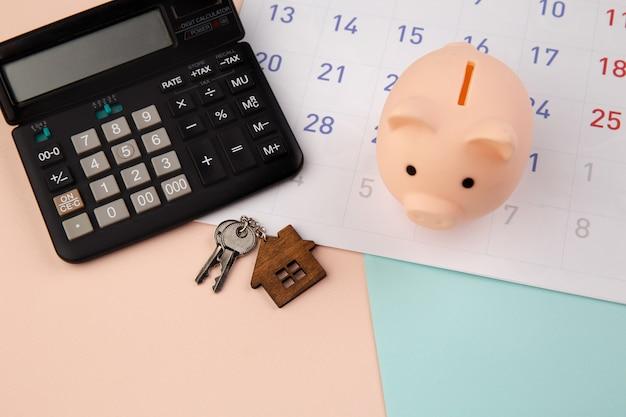 Aankoop van nieuw huis, herinnering aan hypotheekschema of betalingsdag voor onroerend goed, houten huissleutelhanger en spaarvarken met rekenmachine op witte schone kalender.