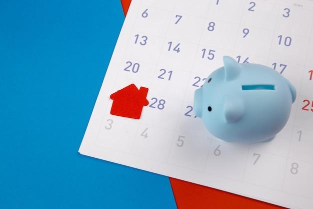 Aankoop van nieuw huis, herinnering aan hypotheekschema of betalingsdag voor onroerend goed, huis en spaarvarken op witte schone kalender.
