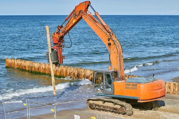 Aanleg van golfbrekers uit boomstammen aan de zeekust.