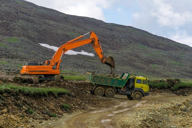 Aanleggen van een weg in bergachtig gebied, een graafmachine en een dumper tijdens bouwwerkzaamheden