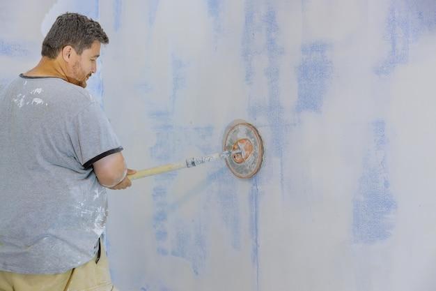 Aannemer die zandtroffel gebruikt die de gipsplaat op de muur schuurt