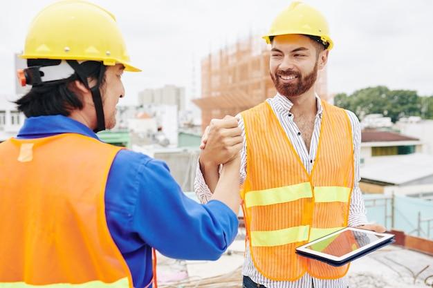 Aannemer en bouwer die handen schudden