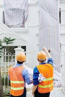 Aannemer en hoofdingenieur bespreken renovatie van gebouwen