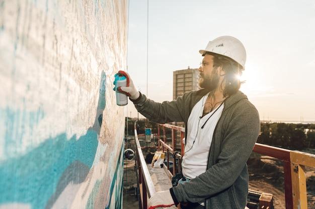 Aannemer, kunstenaar op grote hoogte in een bouwwieg voert gevelschildering, decoratie en woningrenovatie uit