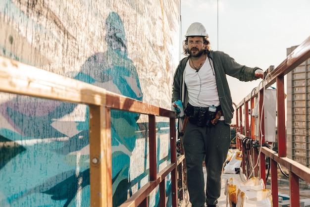 Aannemer, kunstenaar op grote hoogte in een wieg van een gebouw voert gevelschildering uit