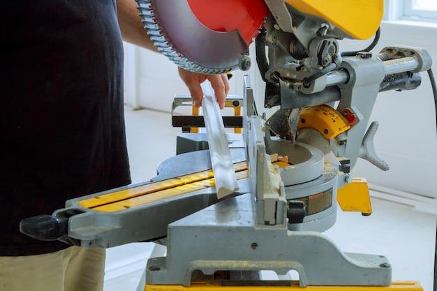 Aannemer met behulp van cirkelzaag snijden crown molding voor renovatie.