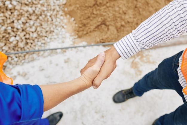 Aannemer steunt de hand van de bouwer om hem te bedanken voor het goede werk, van bovenaf bekeken