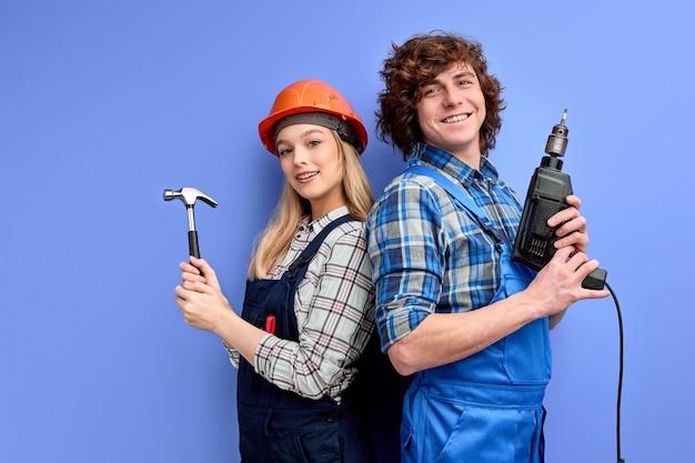 Aannemers-bouwers staan rug aan rug tegen elkaar met huishoudgereedschap