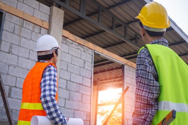 Aannemers en ingenieurs staan te praten en samen te werken binnen het bouwgebied