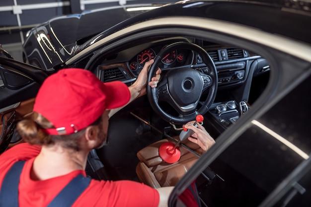 Aanpassing. autodienstmedewerker in rode pet en t-shirt stuurwiel in auto aanpassen, gehurkt in de buurt van open deur van voorstoel
