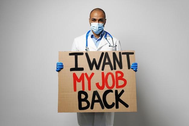 Aanplakbiljet 'ik wil mijn baan terug' in handen van demonstrerende arts met masker.