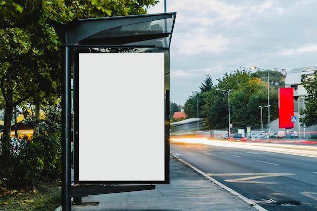 Aanplakbord bij bushalteschuilplaats met vaag spoorlicht
